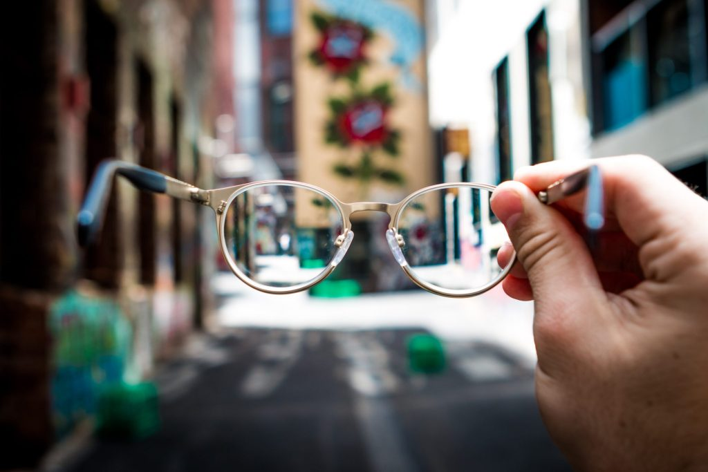 View through a pair of spectacles held out in a person's hand