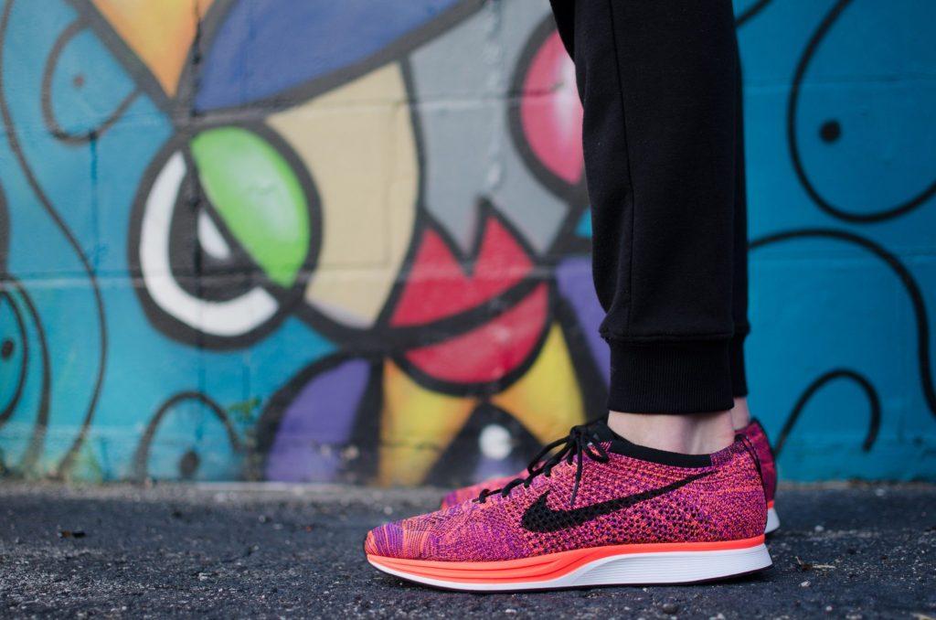 Nike shoes against a graffiti wall  Photo by Hunter Johnson on Unsplash